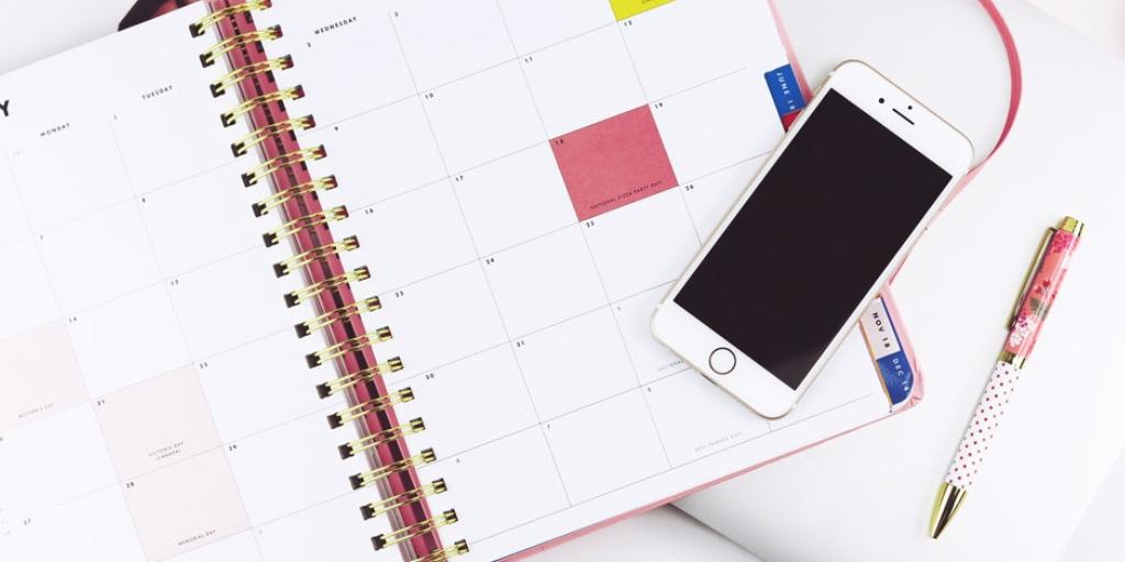 Kalender mit Smartphone und Stift