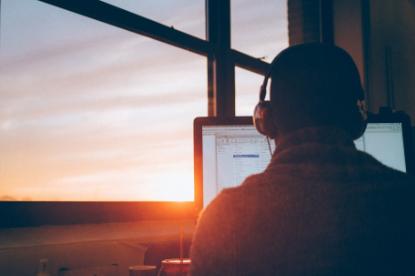 Ein Mann sitzt vor seinem PC und trägt Kopfhörer